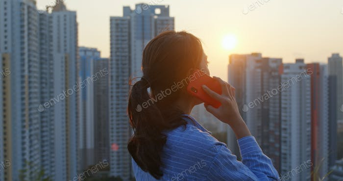 Frau sprechen mit Handy im Hintergrund der Stadt unter Sonnenuntergang Zeit