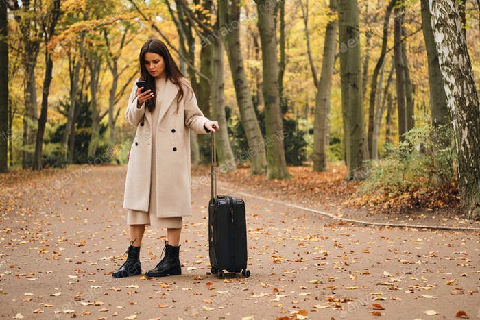 Attractive girl in coat intently using cellphone standing in autumn park with suitcase