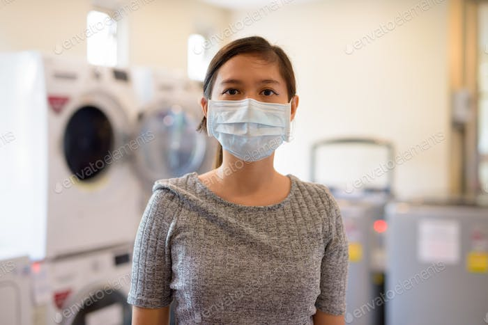 Young Asian woman wearing mask at the laundromat for protection from corona virus outbreak