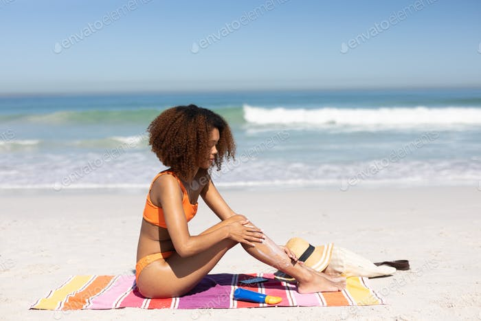 African american woman putting sunscreen on the beach