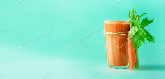 Organic carrot juice with carrots, celery on blue background. Fresh vegetable smothie in glass