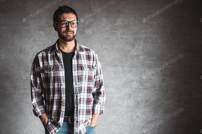 Männer in einem karierten Hemd auf einem Hintergrund der grauen Betonwand