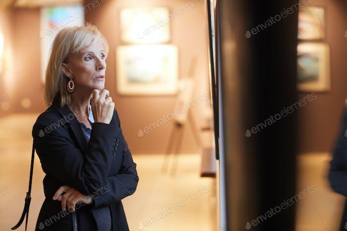 Senior Frau Blick auf Gemälde in Kunstgalerie