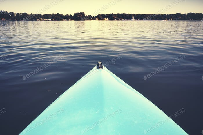 Bow of a kayak on a still lake.