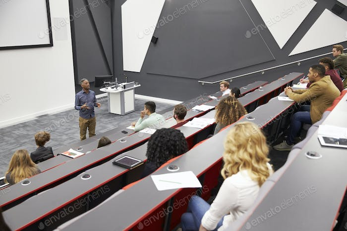 Man lectures students in lecture theatre, mid row seat POV