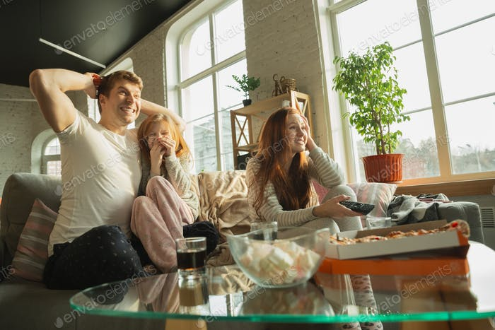 Family spending nice time together at home, looks happy and excited, eating pizza, watching sport