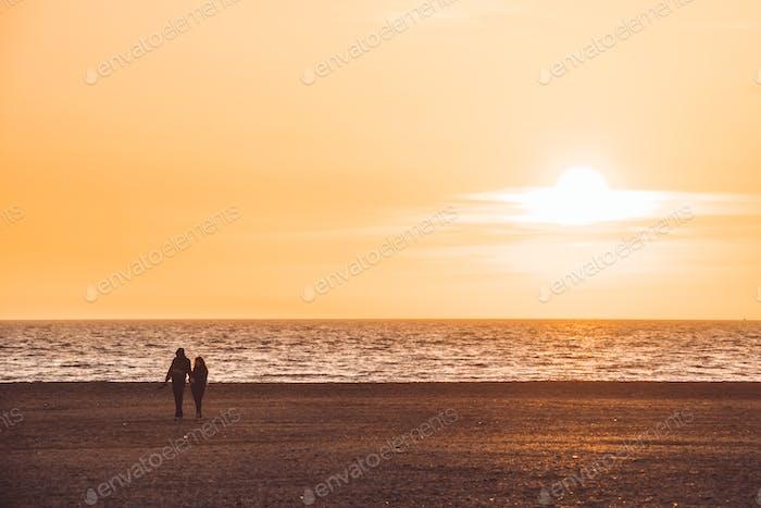 silhouette of couple walking on the beach on orange sunset background, almerimar, almeria, spain