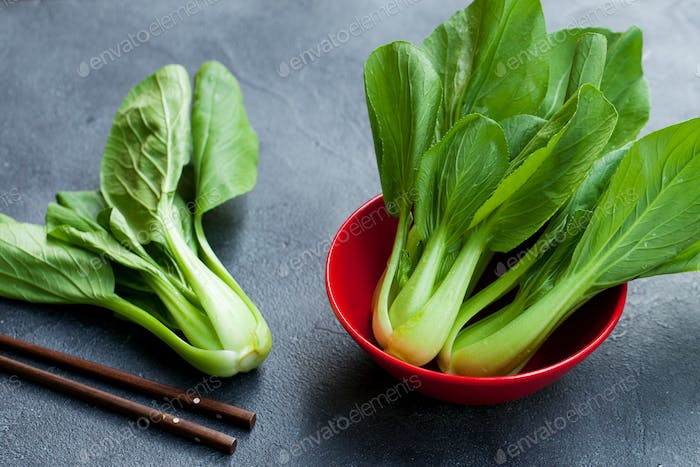 Bok Choy Fresh Salad in a Red Bowl on Grey Table Background. Close up.
