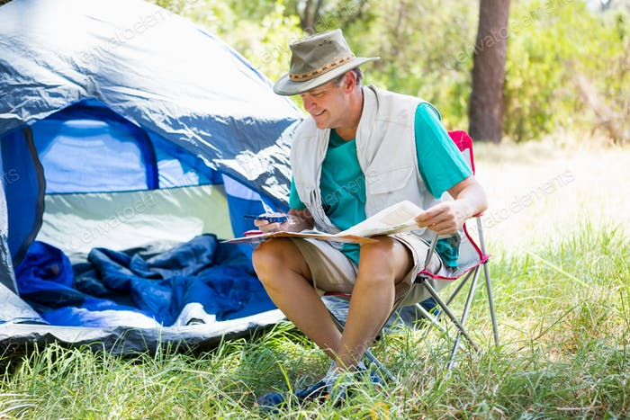 senior man reading beside his tent