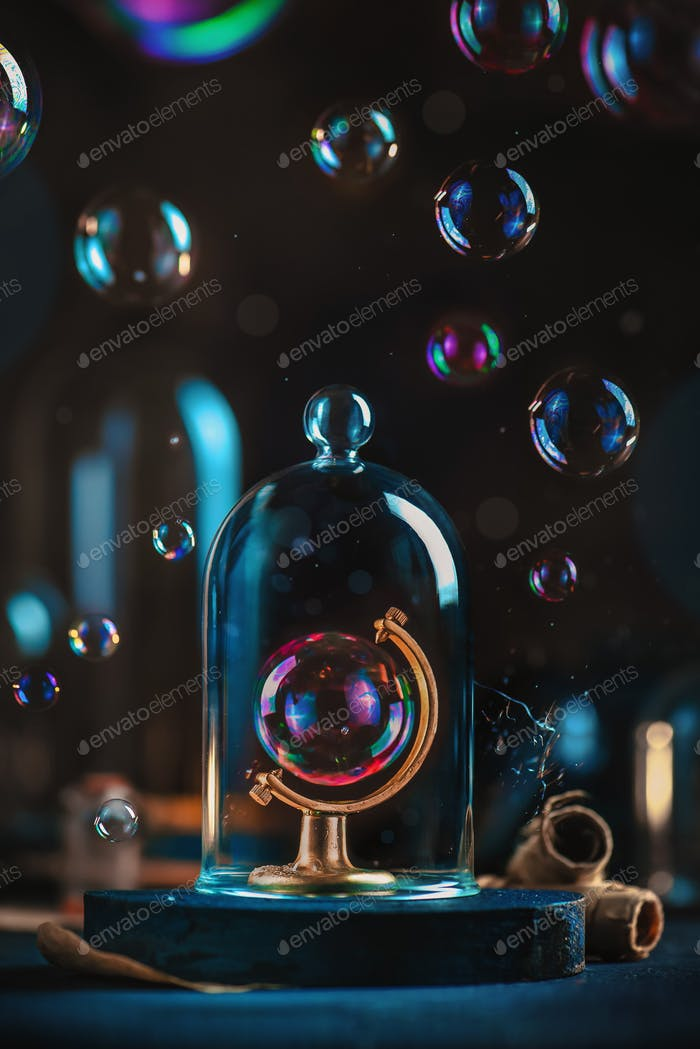 Soap bubble in a globe frame under a glass dome. Ecology and climate change concept.