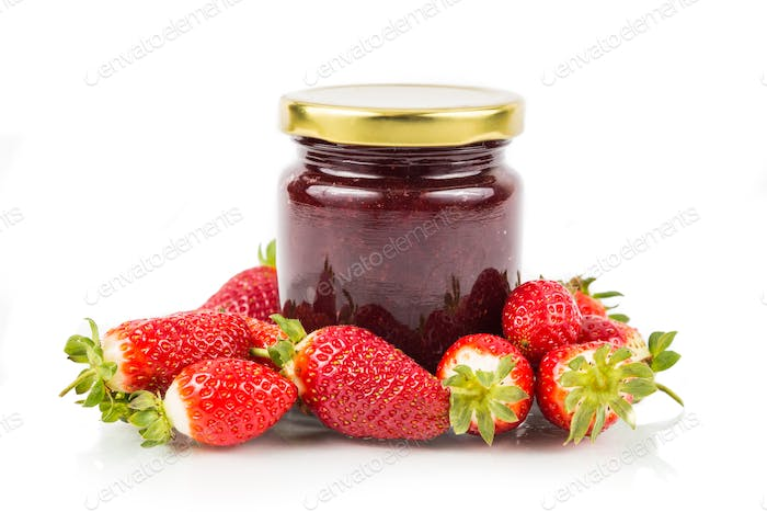Organic strawberry jam in transparent glass jar with fresh straw