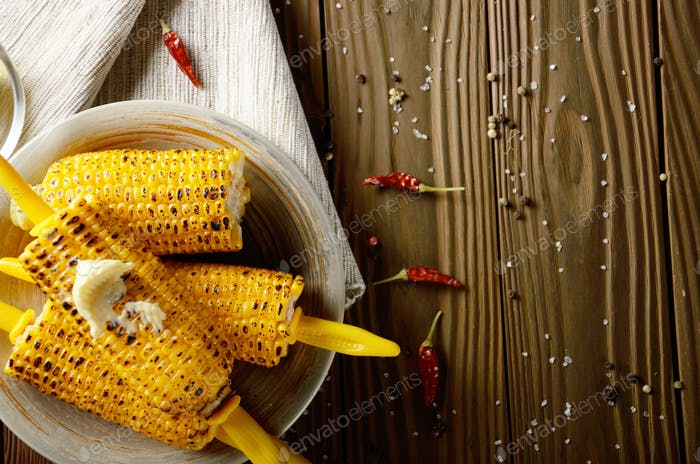 Top view of Wooden table with deep grilled sweet corn cobs under