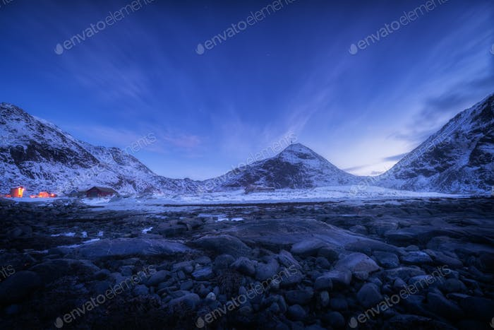 Blue sky with stars rocky beach and snow covered mountains