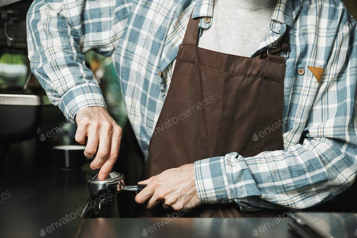 Image of european barista man making coffee while working in caf