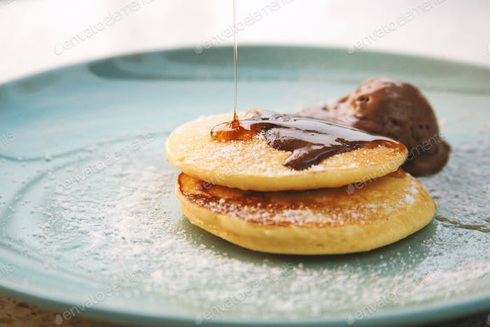 Pancakes pouring with syrup