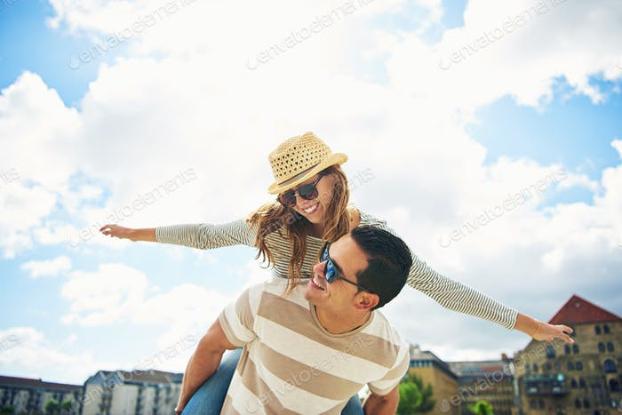 Young couple having fun piggy backing