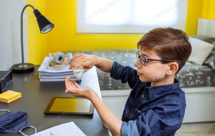 Teenager applying hand sanitizer before doing homework