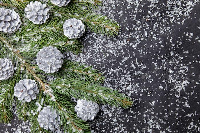 Weihnachtshintergrund mit Tanne und silbernen Zapfen