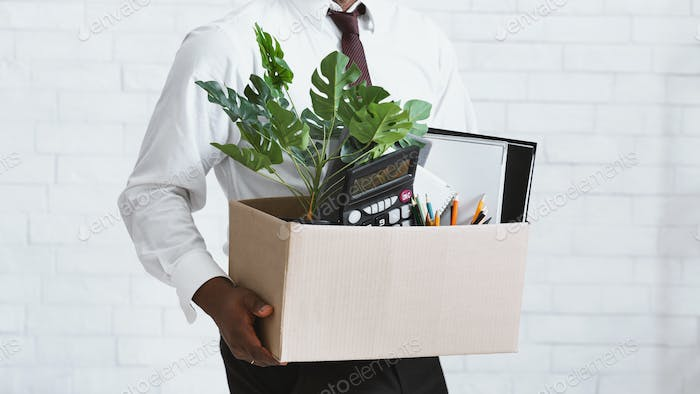 Losing job. Closeup view of African American guy with box of his stuff leaving office