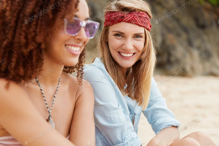 Happy interracial young females support feminsim, have positive expressions, sit together in mountai