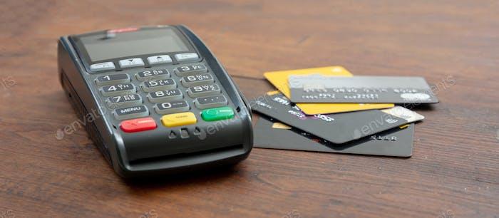 Máquina de pago, terminal POS y tarjetas de crédito en escritorio de madera