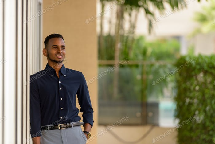 Handsome African businessman outdoors at rooftop garden smiling and thinking