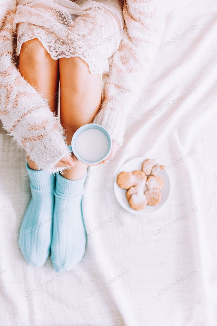Young woman on the bed with with cup of milk in hands enjoys her stay at home.