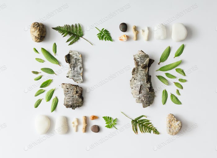 Creative natural layout made of leaves, stones, and tree bark.