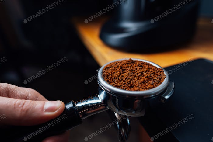portafilter full of ground coffee in a hand