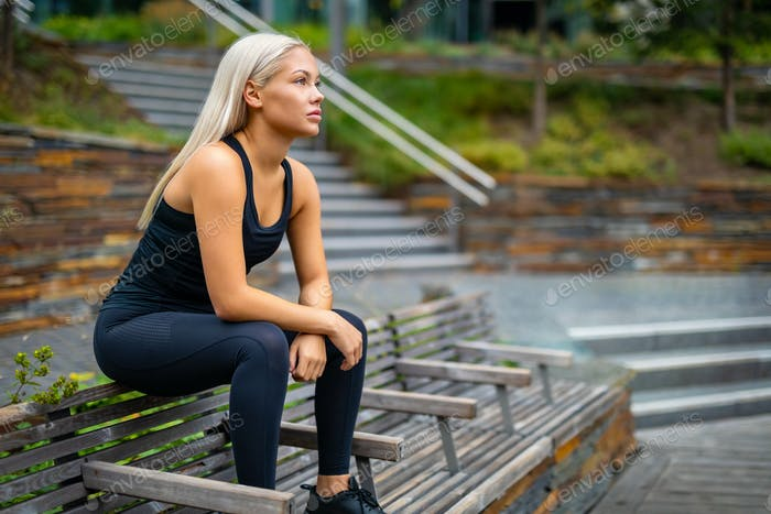 Thoughtful Runner Sitting On Bench After Workout