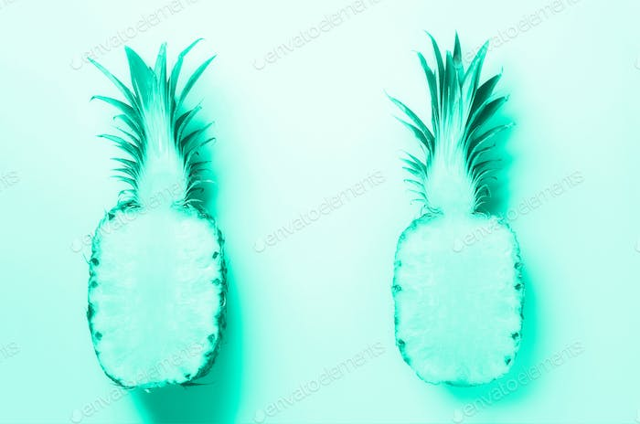 Half of sliced pineapple on mint color background. Top View. Bright pattern for minimal style