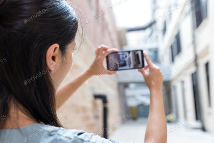 Frau fotografiert auf Handy bei Touristenattraktion