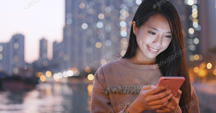 Asiatische Frau Verwendung von Smartphone in der Stadt bei Nacht