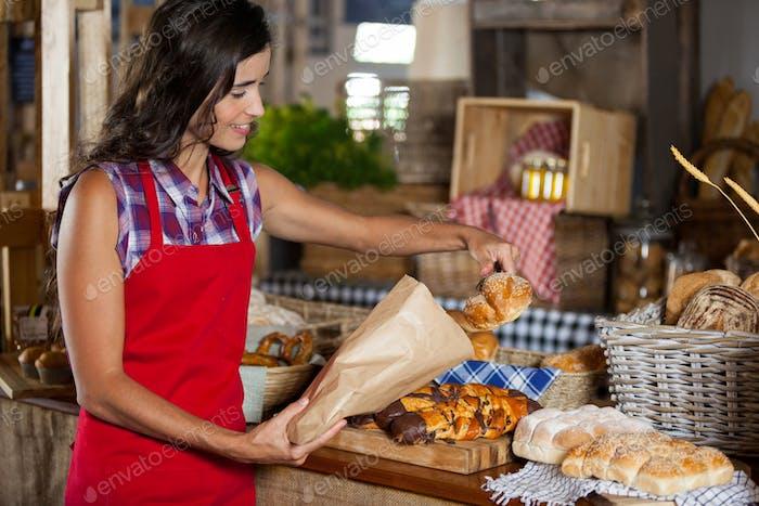 Lächelnde weibliche Mitarbeiter Verpackung süßes Essen in Papiertüte an der Theke
