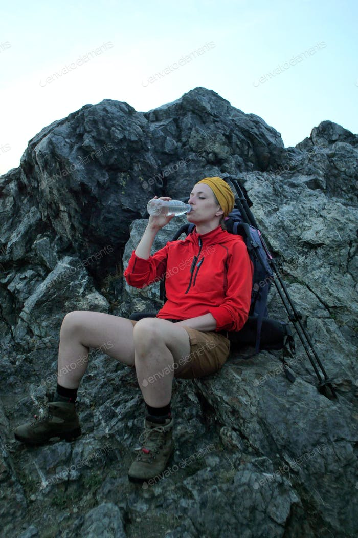 female hiker drinking water