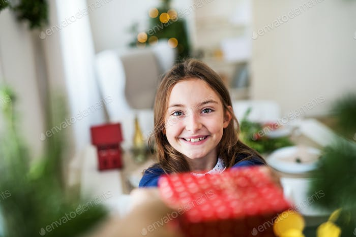 A small girl with a present at home at Christmas time.