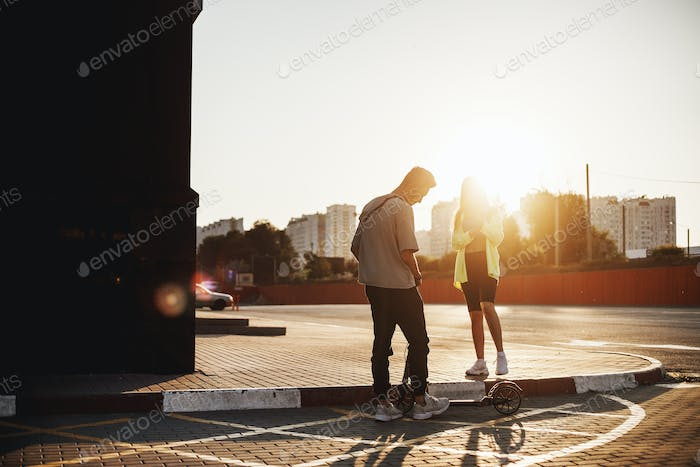 Young stylish guy with scooter and girl are standing together on the square for parking on the sunny