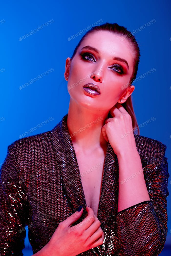 Trendy girl with long hair and stylish makeup in a black shining dress poses on the blue background