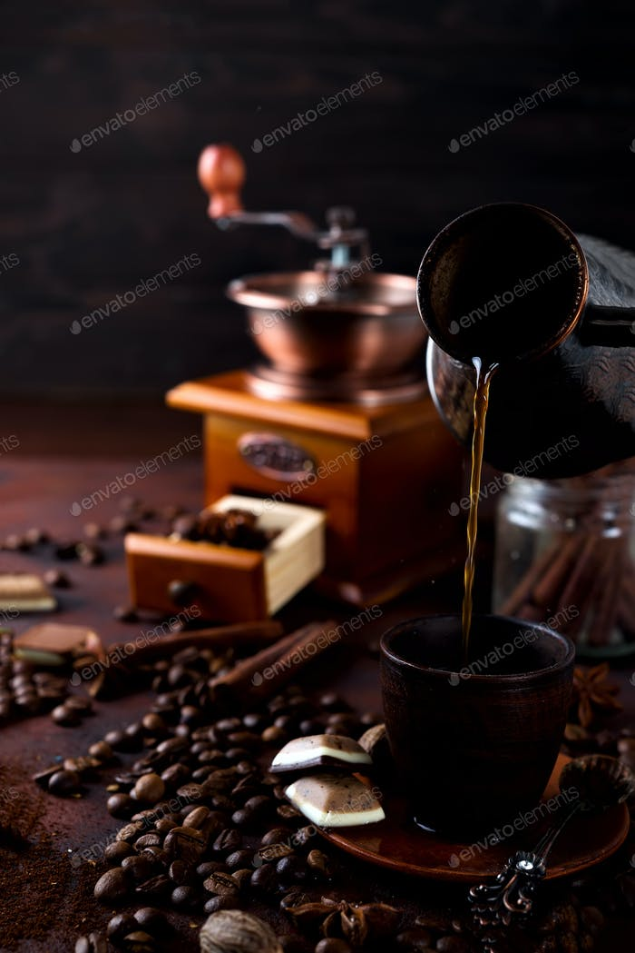 Coffee is pouring to the cup on dark stone background with coffee beans