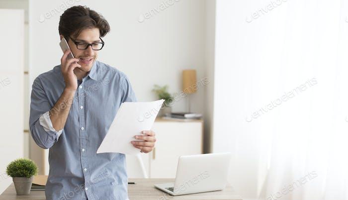 Mann im Gespräch auf Handy hält Papier Benachrichtigung im Büro