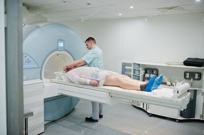 Male doctor turns on magnetic resonance imaging machine with patient inside.