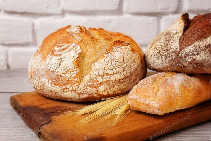 Fresh homemade bread assortment on old cutting board