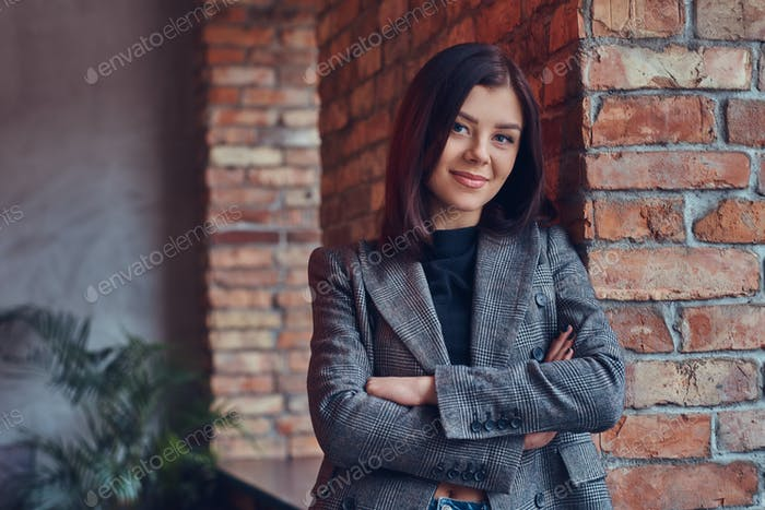 Portrait of a beauty businesswoman leaning against a brick wall