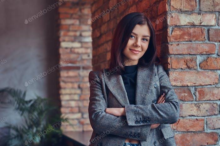 Портрет красавицы, склонившейся к кирпичной стене