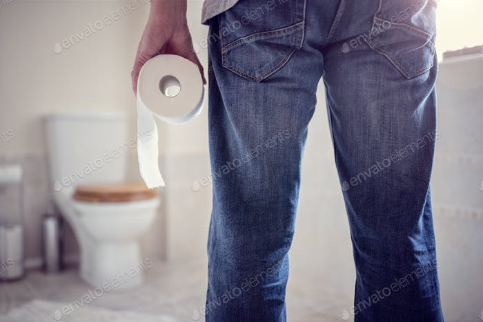 Man holding toilet paper roll in bathroom