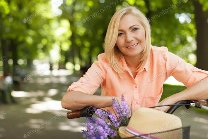 Porträt der schönen Frau mit Fahrrad im Sommertag