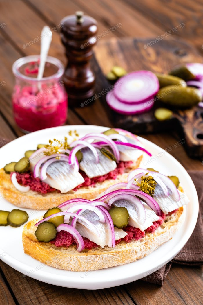 Delicious grilled sandwiches with herring, onion and beetroot sauce with horseradish