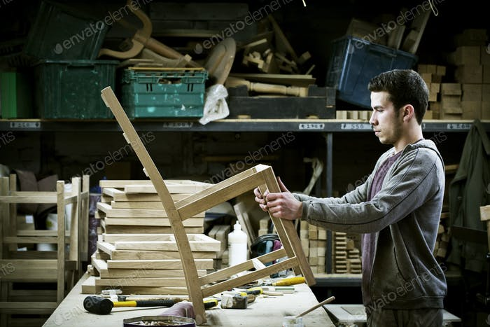 A man working in a furniture maker's workshop.