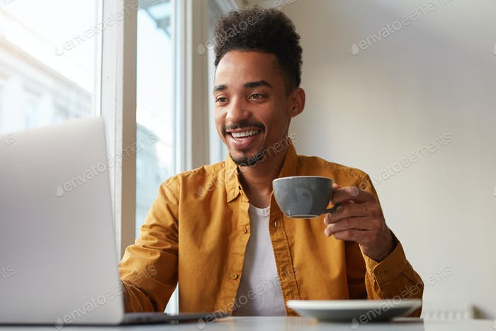 Young African American man uses modern technologies, sits in front of laptop computer