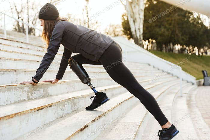 Image of disabled sportswoman with prosthetic leg in tracksuit,